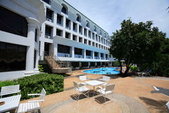 Таблицы на бассейне, loungers солнца рядом с садом и зданиях Стоковая Фотография