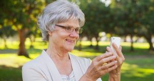 Тазобедренная бабушка принимая selfies на парк стоковое изображение