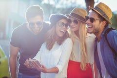 Тазобедренные друзья проверяя на smartphone стоковые изображения