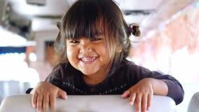 Таиланд, Бангкок, 22-ое декабря 2015 Ребенок дразня девушку на школьном автобусе Счастливая азиатская девушка имеет время потехи  сток-видео