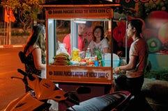 ТАИЛАНД, ПХУКЕТ, 19-ое марта 2018 - концепция еды улицы дешево в Азии Блинчики торговца тележки на улице ночи Покупатели фаст-фуд стоковое фото