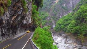 ТАЙВАНЬ - 15-ОЕ МАЯ 2019: Автомобиль такси управляет через скалистый каньон на национальном парке ущелья Taroko в Тайване видеоматериал
