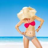 Тайник женщины за соломенной шляпой указывая на солнце нарисованное creme spf Стоковое Изображение