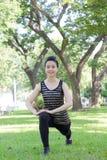 Тайская взрослая красивая девушка делая йогу работает в парке Стоковые Фото