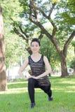 Тайская взрослая красивая девушка делая йогу работает в парке Стоковые Изображения