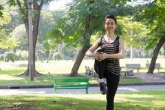 Тайская взрослая красивая девушка делая йогу работает в парке Стоковые Фотографии RF
