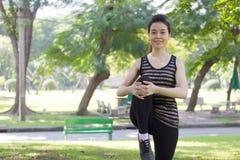 Тайская взрослая красивая девушка делая йогу работает в парке Стоковое Изображение