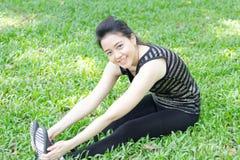 Тайская взрослая красивая девушка делая йогу работает в парке Стоковая Фотография RF