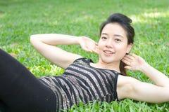 Тайская взрослая красивая девушка делая йогу работает в парке Стоковая Фотография