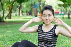 Тайская взрослая красивая девушка делая йогу работает в парке Стоковое Изображение RF