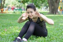 Тайская взрослая красивая девушка делая йогу работает в парке Стоковое фото RF