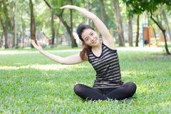 Тайская взрослая красивая девушка делая йогу работает в парке Стоковые Изображения RF