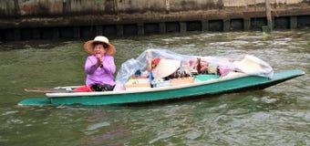 Тайская дама продавая ее товары от маленькой лодки на реке в Бангкоке Стоковое Изображение RF