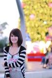 Тайская девушка на предпосылке bokeh желтых светов Стоковая Фотография