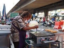 Тайская женщина делает crepes сосиски на местном рынке Стоковое фото RF