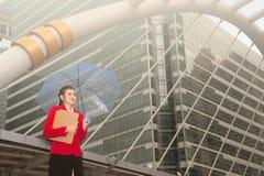 Тайская милая женщина в красном костюме офиса держа зонтик Стоковые Фото
