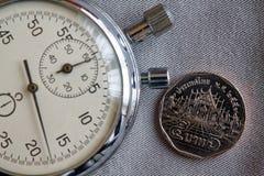 Тайская монетка с деноминацией 5 бат и секундомер на сером фоне джинсовой ткани - предпосылке дела Стоковое Фото