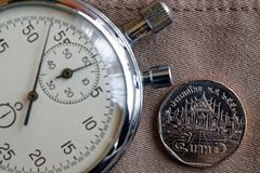 Тайская монетка с деноминацией 5 бат и секундомер на старом бежевом фоне джинсовой ткани - предпосылке дела Стоковые Изображения