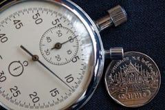 Тайская монетка с деноминацией 5 бат и секундомер на старом черном фоне джинсовой ткани - предпосылке дела Стоковые Фотографии RF