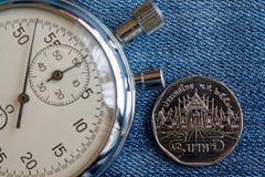 Тайская монетка с деноминацией 5 бат и секундомер на фоне голубых джинсов - предпосылке дела Стоковое Изображение RF