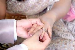 Тайская рука ` s groom кладя обручальное кольцо на палец ` s невесты Стоковые Изображения