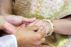 Тайская рука ` s groom кладя обручальное кольцо на палец ` s невесты Стоковое Изображение