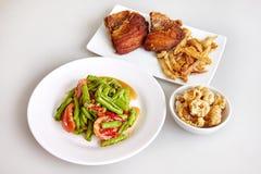 Тайская традиционная еда, длинный салат фасоли пряный, при зажаренные рыбы тилапии, кудрявая кожа свинины, белая предпосылка - вз стоковые фотографии rf