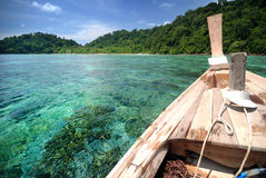 Тайская шлюпка плавая на ясную воду над рифом Стоковое фото RF