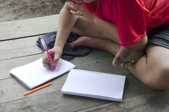 Тайские дети изучают и домашняя работа сочинительства на тетради на деревянном t Стоковое Фото