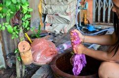 Тайские женщины связывают батик крася красный и розовый естественный цвет сделанный от Стоковые Изображения