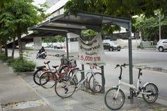 Тайские люди останавливают и фиксируют велосипед на автостоянке велосипеда около дороги Стоковое Изображение
