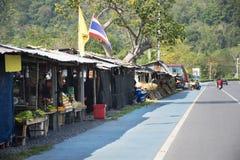 Тайские люди управляя автомобилем на дороге на сельской местности с местным магазином для людей ходя по магазинам на около дороге стоковое изображение