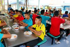 Тайские студенты сидя в буфете школы ждать для еды их l стоковая фотография