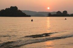 Тайские люди устанавливая рыболовные сети перед малой водой на заходе солнца Стоковые Фото