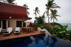 Тайский бассейн вилл, loungers солнца рядом с садом внутри залив океана Стоковое фото RF