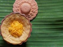 Тайский десерт, заварной крем яичка с сладостным липким рисом покрыл с золотыми потоками, на предпосылке лист банана стоковая фотография rf