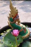 Тайский зеленый дракон и маленький фиолетовый лотос Стоковая Фотография