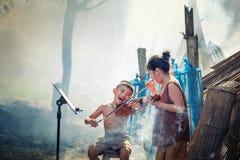 Тайский мальчик и сельские девушки играя скрипку на ее домашнем саде это Стоковое Изображение RF