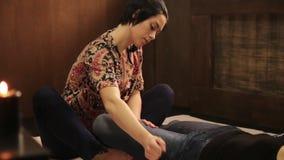 Тайский массаж ноги в салоне курорта Профессиональный masseur делая традиционный тайский массаж для женского клиента сток-видео