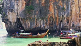 Тайский поплавок шлюпки Longtail к морю от пляжа против скалистой скалы сток-видео