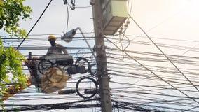 Тайский работник для того чтобы изменить новую кабельную линию связи на поляке электричества внутри Стоковая Фотография
