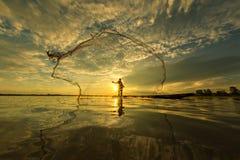Тайский рыболов на деревянной шлюпке бросая сеть стоковые изображения rf