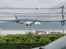 Тайский самолет авиалинии приземляется на международный аэропорт Чиангмая, Чиангмай, Таиланд, летая низко над улицей с traffi стоковая фотография rf