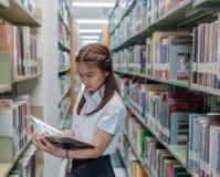 Тайский студент девушки в форме читая книгу в библиотеке Стоковые Изображения