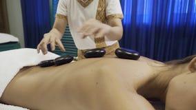 Тайский терапевт делая массаж с горячими камнями видеоматериал