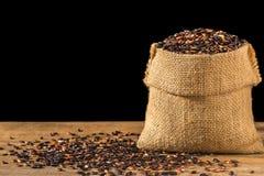 Тайский черный липкий рис в малом мешке на деревянном столе Стоковое Изображение RF