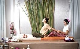 Тайский Masseuse делая массаж для женщины в салоне курорта Азиатская красивая женщина получая тайский травяной массаж обжатия мас стоковое фото
