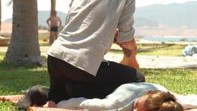 Тайское massagiste делая протягивающ массаж женской ноги внешний Женщины получая курс массажа йоги Обработка и сток-видео