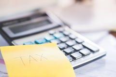 Таксируйте столб слова оно примечание и калькулятор, концепция сезона налога Стоковое фото RF