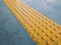 Тактильный вымощать или Tenji блок на земной поверхности как наведение или обнаруженное предупреждение для того чтобы помочь пеше стоковая фотография